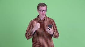 Счастливый молодой человек хипстера используя телефон и давать большие пальцы руки вверх акции видеоматериалы