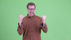 Счастливый молодой человек хипстера поворачивая вокруг и получая хорошие новости видеоматериал