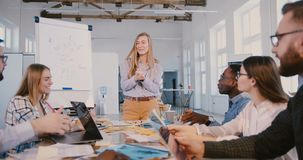 Счастливый молодые белокурые женские специалист по маркетингу и тренер говоря, мотируя работники на современном тренировочном сем акции видеоматериалы