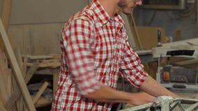 Счастливый мужской плотник представляя с куском дерева на его мастерской видеоматериал