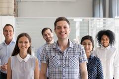 Счастливый мужской руководитель, тренер представляя с multiracial группой в составе использует стоковая фотография rf