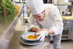 Счастливый мужской шеф-повар варя еду на кухне ресторана Стоковые Изображения RF