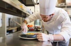 Счастливый мужской шеф-повар варя еду на кухне ресторана Стоковые Изображения
