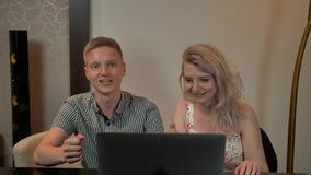 Счастливый мужчина и женский усмехаться пока смотрящ таблетку рукоятка детализировала ее домашний взгляд крыто акции видеоматериалы