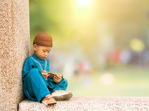счастливый мусульманский ребенк при парадный костюм играя умный телефон стоковые фото