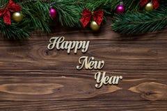 Счастливый Новый Год в центре  деревянной предпосылки с ветвями сосны на верхней части экрана Стоковая Фотография RF