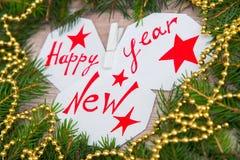 Счастливый Новый Год написанный на белых листах Стоковая Фотография