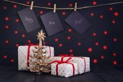 Счастливый Новый Год на бумаге при зажимка для белья, вися на веревочке на темной деревянной предпосылке Поздравительная открытка Стоковое фото RF