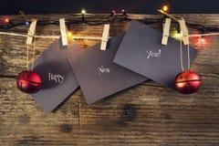 Счастливый Новый Год на бумаге при зажимка для белья, вися на веревочке на деревянной предпосылке Поздравительная открытка с счас Стоковое Изображение RF