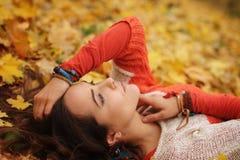 Счастливый отдыхая портрет девушки, лежа в кленовых листах осени в парке, закрыл глаза, одетые в свитере моды стоковые фотографии rf