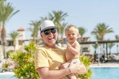 Счастливый отец держа жизнерадостного сына во время тропических кани стоковое фото rf