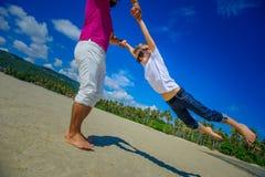 Счастливый отец закручивает в круг его прелестного мальчика Солнечное tropi Стоковые Фотографии RF