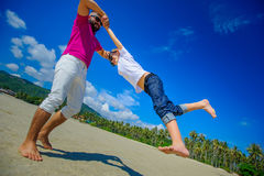 Счастливый отец закручивает в круг его прелестного мальчика Солнечное tropi Стоковое Фото