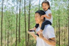 Счастливый отец и дочь играя снаружи в зеленом лесе стоковое изображение