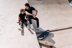 Счастливый отец и его сын одетые в случайных одеждах сидящ и смеющся на скольжении в парке конька рядом с стоковые фото