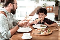 Счастливый отец и сын имея обед в кафе есть yummy пиццу стоковые изображения rf