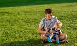 Счастливый отец и сын имея потеху внешнюю на луге стоковая фотография