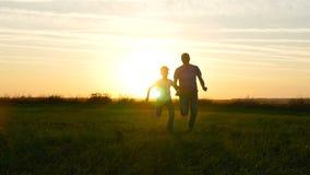 Счастливый отец и сын семьи бежать через зеленое поле против предпосылки захода солнца