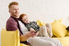 счастливый отец и сын сидя совместно на софе и используя удаленный регулятор пока смотрящ ТВ стоковая фотография rf