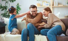 Счастливый отец матери семьи и дочь ребенка смеясь дома стоковые фото