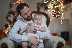 Счастливый отец обнимая его дочь младенца для рождественской елки освещает на заднем плане стоковое изображение