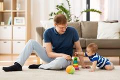 Счастливый отец с меньшим сыном младенца играя дома стоковые фотографии rf