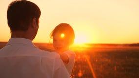 Счастливый папа и маленькая дочь сидя в ее оружиях на солнце захода солнца ярком Смех девушки играя с папой на выравнивать прогул стоковое изображение rf