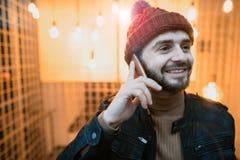 Счастливый парень битника говоря на smartphone На фоне ламп Стоковое Изображение RF