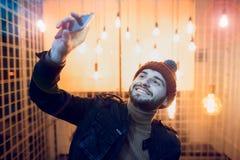 Счастливый парень битника делая фото selfie на фоне ламп Стоковая Фотография RF
