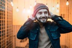 Счастливый парень битника на фоне ламп Держит его руки к шляпе Стоковое Фото