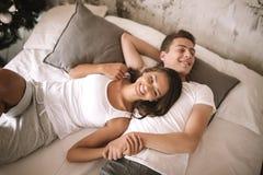 Счастливый парень и девушка одетые в белых футболках лежат на кровати с белым одеялом с серыми подушками и держат руки стоковая фотография rf