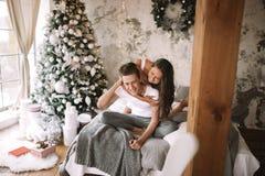 Счастливый парень и девушка одетые в белых футболках сидящ и обнимающ на кровати с серым украшенным одеялом в уютном стоковые изображения