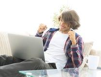 Счастливый парень при компьтер-книжка сидя на кресле успех результатов диаграммы принципиальной схемы бизнесменов Стоковые Изображения RF