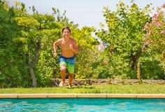 Счастливый подросток бежать к бассейну стоковые изображения