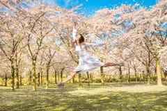 Счастливый подросток он смеющся над и скачущ вверх в blossoming cherr стоковая фотография
