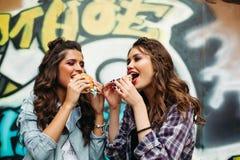 Счастливый подросток при стили причёсок есть обед в улице стоковое фото rf