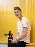 Счастливый подросток с скейтбордом на желтой предпосылке Вскользь, беспечальное, милое, смеясь над снаружи парня расслабляющее Стоковое Изображение