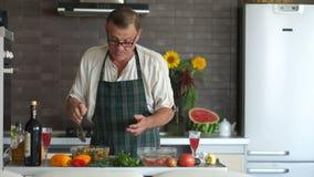 Счастливый пожилой гражданин пробует салат в его кухне и танцует с удовольствием Здоровый образ жизни, правильное питание, vegan акции видеоматериалы
