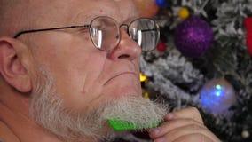 Счастливый пожилой человек расчесывая его серую бороду с гребнем на предпосылке рождественской елки в гирляндах, зеленых шариках  сток-видео