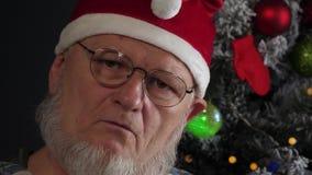 Счастливый пожилой человек с серыми бородами принимает медицину и выпивает планшеты с водой на предпосылке рождественской елки в  сток-видео