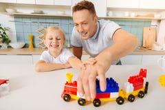 Счастливый положительный человек держа поезд игрушки Стоковое фото RF