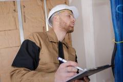 Счастливый построитель в защитном шлеме с доской сзажимом для бумаги на строительной площадке Стоковое Изображение RF