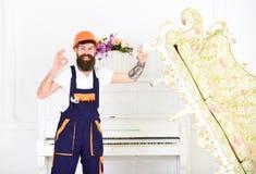 Счастливый построитель передислоцируя винтажную софу перед redecoration Усмехаясь движенец с стильной бородой и усик показывая о' Стоковые Изображения