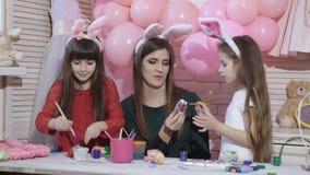 счастливый праздник Мать и ее дочери красят яйца подготовлять семьи пасхи Милые девушки маленьких детей видеоматериал