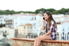 Счастливый предназначенный для подростков говорить по телефону сидя на уступе стоковые изображения
