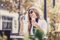 Счастливый предприниматель работая с телефоном, компьтер-книжкой и выпивая caf Стоковое Изображение