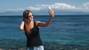 Счастливый путешественник девушки в солнечных очках делает selfie на телефоне, океане на предпосылке видеоматериал