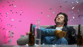 Счастливый пьяный парень охлаждая вне на кресле на партии, confetti падая вниз, ослабляет акции видеоматериалы