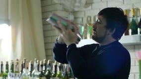 Счастливый работник бара с шейкером в оружиях смешивает конец-вверх ингридиентов на предпосылке интерьера бара сток-видео
