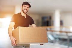 Счастливый работник доставляющий покупки на дом с коробкой стоковое фото rf